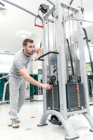 loads: More weight. Confident athlete trainer weight loads. A young man in the gym before work involved in sports. The model is looking forward. Stock Photo