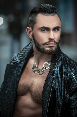 Handsome beard man posing in leather raincoat. Leather pants and glasses making it look unforgettable. Fashionable hairstyle in his style Standard-Bild