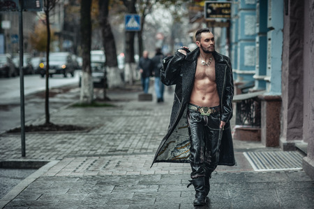 Handsome beard man posing in leather raincoat. Leather pants and glasses making it look unforgettable. Fashionable hairstyle in his style Stock Photo