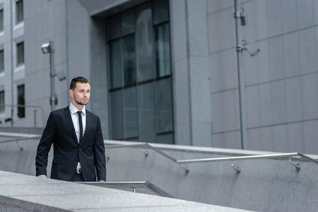 seguir adelante: Seguir adelante. El hombre de negocios joven y talentoso va a cumplir su sue�o. Un hombre con barba en un traje Foto de archivo