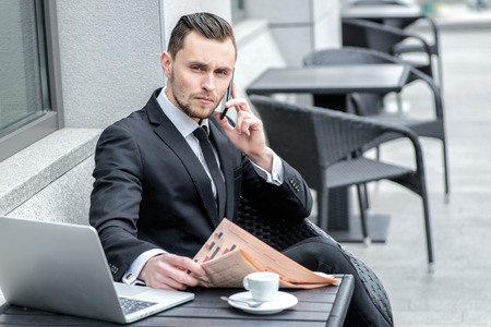 Serious conversation. Businessman sitting at a laptop and mobile phone in his hand on the table and laptop. photo