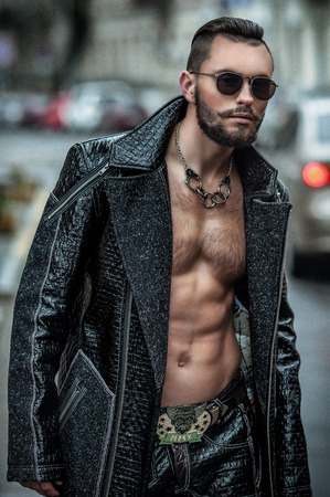 Handsome beard man posing in leather raincoat. Leather pants and glasses making it look unforgettable. Fashionable hairstyle in his style photo