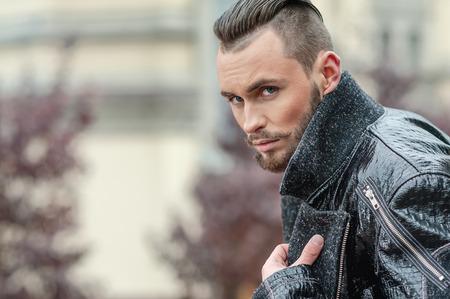 Homme élégant debout sur la rue dans un manteau de cuir.
