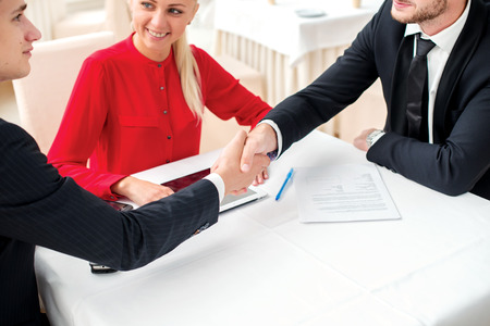 Confident transactions. Three successful and confident businessman shaking hands. Businesspeople in formal dress sitting in an office at a desk and smiling at the camera photo