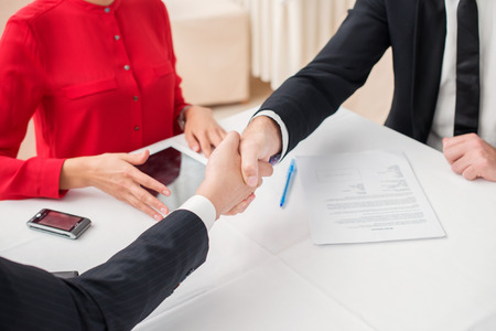 Merger. Three successful and confident businesspeople shake hands. Businesspeople in formal dress sitting in an office at a desk close-up view of hands photo