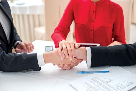 Teamwork. Drie succesvolle en zekere zakenmensen schudden handen. Zakenmensen in formele kledijzitting in een bureau bij een mening van het bureauclose-up van handen