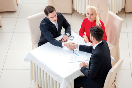 Signing the contract. Three successful and confident businesspeople shake hands. Businesspeople in formal attire sitting in an office at a desk and smiling at the camera photo