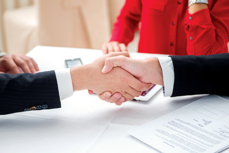 The agreement was signed. Three successful and confident businesspeople shake hands. Businesspeople in formal attire sitting in an office at a desk close-up view of hands photo