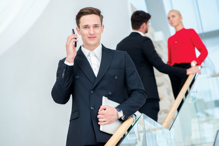 Businessman talking on the phone with a client. Young businessman standing on the steps and keeps the tablet while his colleagues talking to each other photo