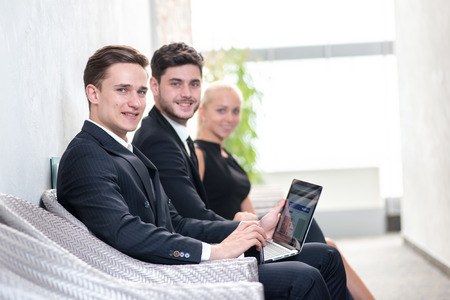 Job candidates. Three people in formalwear waiting in line while sitting at the chairs and holding laptop in their hands photo