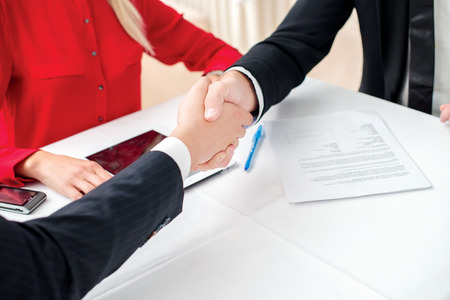 Best Trade. Three successful and confident businessman shaking hands. Businesspeople in formal dress sitting in an office at a desk close-up view of hands photo