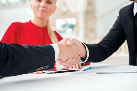 Partnership. Three successful and confident businesspeople shake hands. Businesspeople in formal dress sitting in an office at a desk close-up view of hands photo