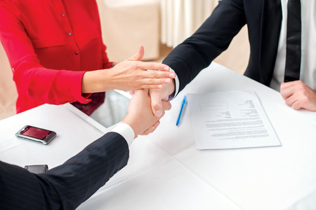 Resolve the dispute. Three successful and confident businesspeople shake hands. Businesspeople in formal dress sitting in an office at a desk close-up view of hands photo