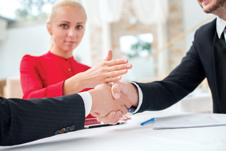 New contract. Three successful and confident businesspeople shake hands. Businesspeople in formal dress sitting in an office at a desk and smiling at the camera photo