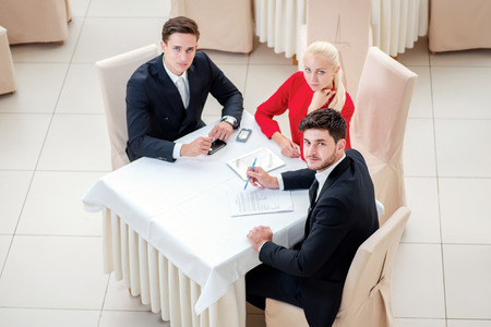 Business partners at the meeting. Top view of the Three businessman sitting at table in formal wear and looking at the camera. photo