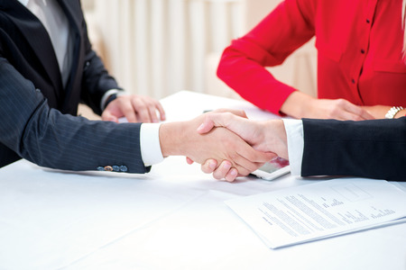 Confirmation of sponsorship. Three successful and confident businesspeople shake hands. Businesspeople in formal attire sitting in an office at a desk close-up view of hands photo