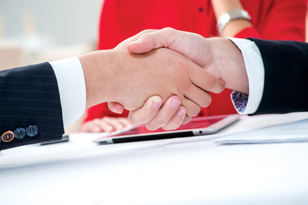 Best partners. Three successful and confident businesspeople shake hands. Businesspeople in formal attire sitting in an office at a desk close-up view of hands photo