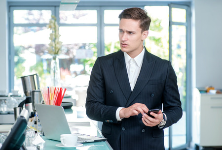 businessman waiting call: Call Waiting. Confident and successful businessman standing in an office and holding a mobile phone in his hand looking away