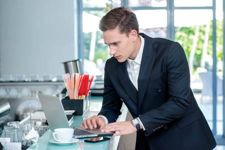 Work laptop. Confident and successful businessman standing in an office and is working at the computer looking to side while drinking coffee photo