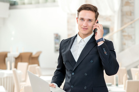 Working in the office. Confident and successful businessman standing in an office and talking on cell phone looking at the camera and smiling while holding a laptop in his hand photo