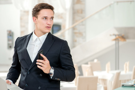 Meeting with a client. Confident and successful businessman standing in an office and talking on mobile phone looking away and smiling while holding a laptop in his hand photo