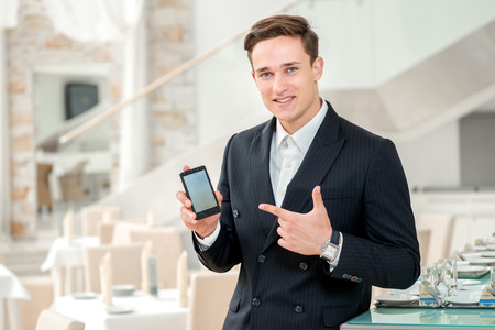 Mobile phone a friend for businessman. Confident and successful businessman in a strict dress standing in an office and holding a mobile phone and points a finger at him photo