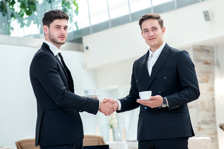 Shaking hands. Two other businessman drinking coffee and talking to each other while standing in an office and smiling to each other photo