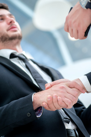 Shaking hands. Two confident businessman shaking their hands and talking to each other while standing in an office and smiling to each other photo