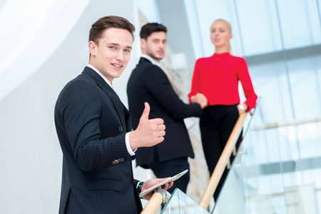 Successful and confident businessman. Young businessman standing on the steps and keeps the tablet and a thumbs-up while his colleagues talk and shake hands with each other photo
