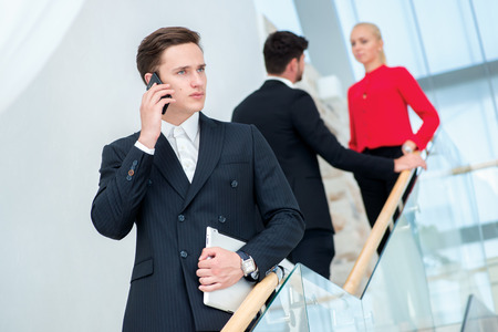Businessman talking on the phone. Young businessman standing on the steps and keeps the tablet while his colleagues talking to each other photo