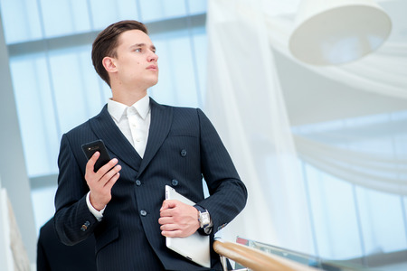 Businessman holding a mobile phone. Young businessman standing on the steps and keeps the tablet while it parnery talk to each other photo