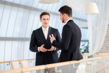 Two successful and confident businessman talking in an office photo