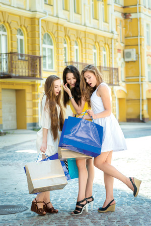 Best shopping trip. Drie aantrekkelijke jonge meisje met boodschappentassen terwijl overweegt de aankoop van pakketten Stockfoto