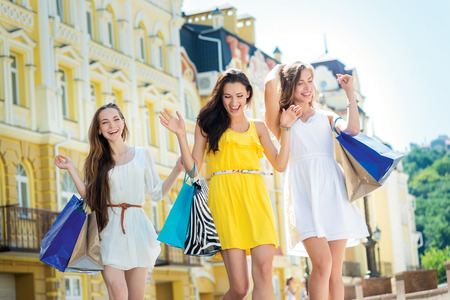 Best shopping for girls. Three attractive young girl holding shopping bags while walking on the street laughing and smiling.