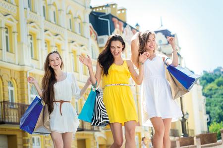 Beste winkels voor meisjes. Drie aantrekkelijke jonge meid die boodschappentassen tijdens het lopen op de straat lachen en glimlachen. Stockfoto