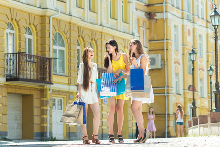 fun day: Fun day for shopping. Three attractive young girl holding shopping bags while walking on the street laughing and smiling.