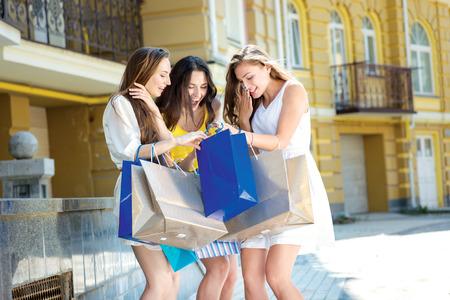 Winkelen shopaholics. Drie aantrekkelijke jonge vrouwen die boodschappentassen en discussiëren over hun aankoop. Meisjes lachen en glimlachen en hand in hand. Stockfoto