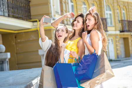 Girls doing selfie. Girls holding shopping bags and walk around the shops. Smiling girl photographed on a cell phone. Girlfriends waving. photo
