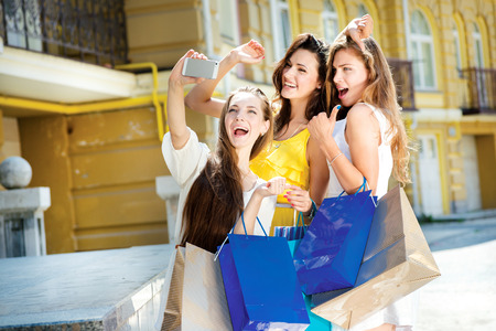 Making Selfie on shopping. Three attractive young girl holding shopping bags while being photographed on a cell phone. Girls laughing and smiling at the camera
