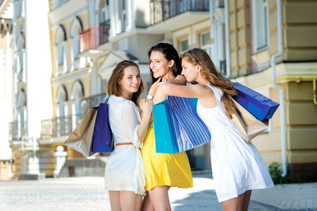 Hugging girlfriends. Three attractive young girl holding shopping bags while pass near the shop and petting. View from the back of girls photo