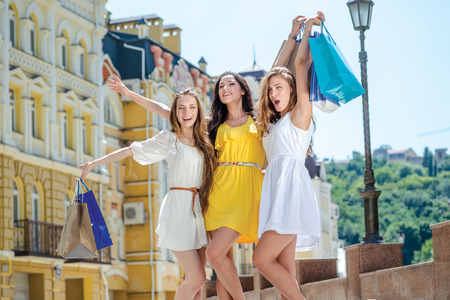 joyfull: Happy shopaholics girlfriend. Three girlfriends holding shopping bags and review their purchases outside the shop. Smiling girlfriends having fun together walking on the street Stock Photo