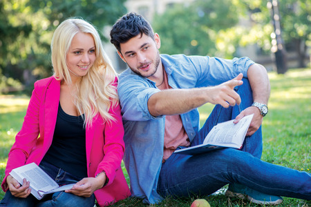 Interrupt academically. Couple of students sitting on the grass and smiling at the camera while teaching lessons on a break near the building of the university. Man points a finger at the teacher photo