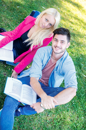 Enjoying university life. Student girl and boy student holding books and looking  at the camera while sitting on the grass near the building of the university on a break. photo