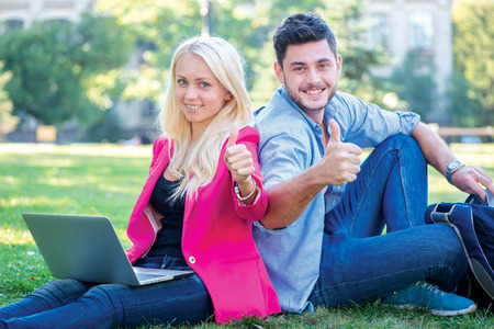 Students break. Student girl and boy student hold a laptop and looking at the camera while sitting on the grass near the campus of the University at the break. Couple showing thumbs up. photo