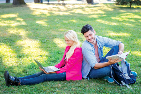 Stay after school. Student girl and boy student hold a laptop and looking at the camera while sitting on the grass near the campus of the University at the break. Couple showing thumbs up. photo