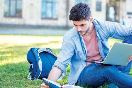 De voorbereiding voor tests. Leuke mannelijke student die een laptop en het lezen van een boek zittend op het gras in de buurt van de campus van de universiteit op het scorebord. Stockfoto