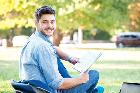 Sweet university life. Cute male student holding a laptop and reading a book and looking away while sitting on the grass near the campus of the University at the break. photo