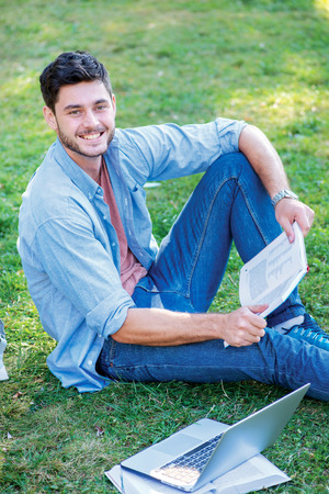 Best day at the university. Cute male student holding a book and looking at the camera while sitting on the grass near the campus of the University at the break. photo