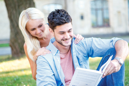 Cheerful university life. Couple in love together students learn lessons and read a book while sitting on the grass against the building of the university photo