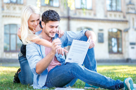 Shared love of learning. Couple in love together teach lessons and read a book while sitting on the grass against the building of the university photo